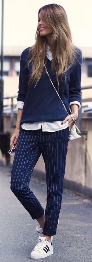 Cómo combinar: jersey de pico azul marino, camisa de vestir blanca, pantalón de vestir de rayas verticales azul marino, tenis blancos