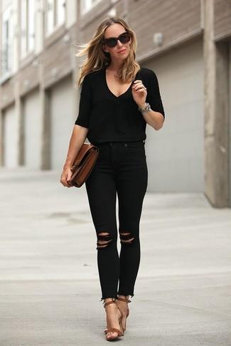 Cómo combinar: jersey de pico negro, vaqueros pitillo desgastados negros, sandalias de tacón de cuero marrónes, cartera sobre de cuero marrón