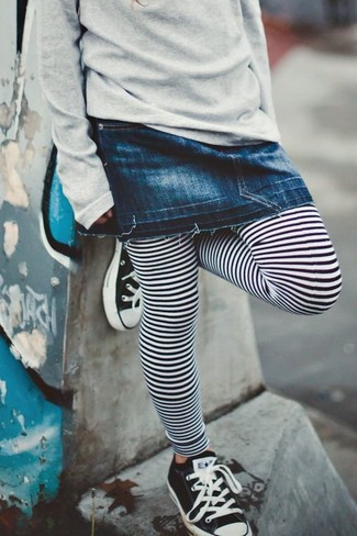 Cómo combinar: jersey gris, falda vaquera azul marino, leggings de rayas horizontales en blanco y negro, zapatillas en negro y blanco
