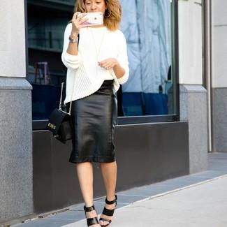 Cómo combinar: jersey oversized de punto blanco, falda lápiz de cuero negra, sandalias de tacón de cuero negras, bolso bandolera de cuero negro