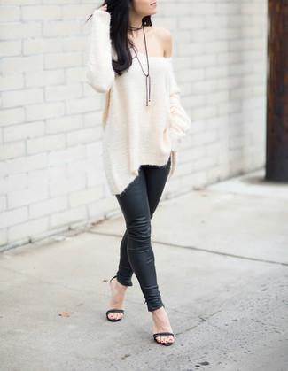 Cómo combinar: jersey oversized de punto blanco, leggings de cuero negros, sandalias de tacón de cuero negras