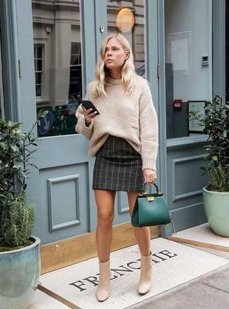 Cómo combinar: jersey oversized de punto en beige, minifalda a cuadros en gris oscuro, botines de cuero en beige, bolsa tote de cuero verde oscuro