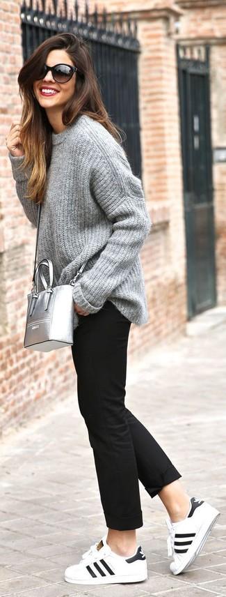 Cómo combinar: jersey oversized de punto gris, pantalón chino negro, tenis de cuero en blanco y negro, bolso bandolera de cuero plateado