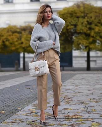 Cómo combinar: jersey oversized gris, pantalón de vestir marrón claro, zapatos de tacón de ante de leopardo blancos, bolso de hombre de cuero acolchado blanco