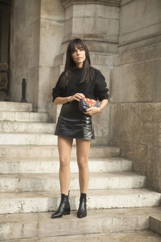 Cómo combinar: jersey oversized negro, minifalda de cuero negra, botines chelsea de cuero negros, cartera sobre de cuero estampada negra