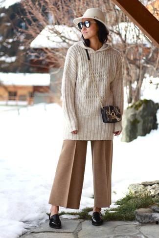 Cómo combinar: jersey oversized de punto en beige, pantalones anchos marrón claro, mocasín de cuero negros, bolso bandolera de cuero con print de serpiente negro