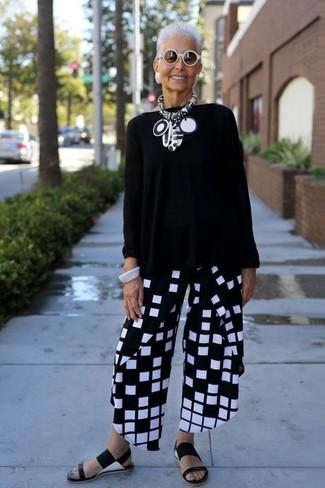 Cómo combinar: jersey oversized negro, pantalones anchos a cuadros en negro y blanco, sandalias planas de cuero negras, gafas de sol blancas