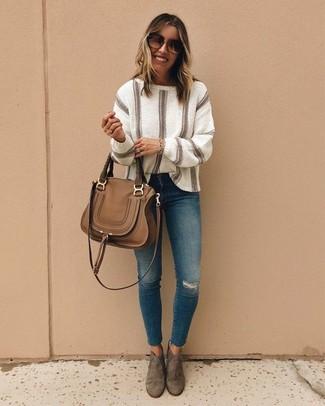 Cómo combinar: jersey oversized de rayas verticales en beige, vaqueros pitillo desgastados azules, botines de ante marrónes, bolso de hombre de cuero marrón