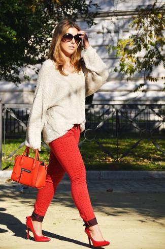 Cómo combinar: jersey oversized en beige, vaqueros pitillo rojos, zapatos de tacón de cuero rojos, cartera de cuero roja