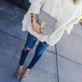 Cómo combinar: jersey oversized de punto blanco, vaqueros pitillo desgastados azul marino, zapatos de tacón de cuero grises, bolso bandolera de cuero gris