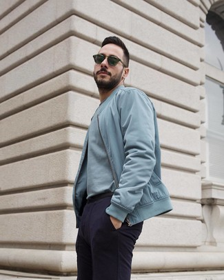 How to wear: light blue bomber jacket, light blue crew-neck t-shirt, navy chinos, dark green sunglasses