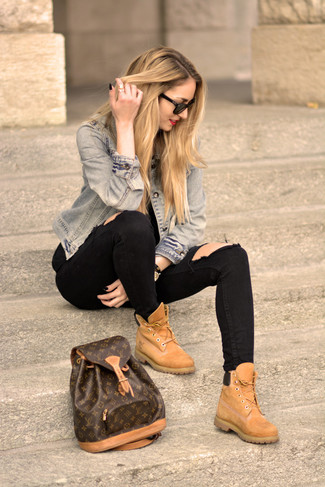 A light blue jean jacket and black distressed slim jeans are a great outfit formula to have in your arsenal. This outfit is complemented perfectly with tan suede lace-up boots.