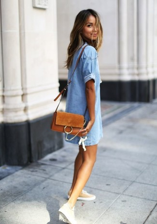 How to Wear a Tobacco Suede Crossbody Bag: A light blue denim shift dress and a tobacco suede crossbody bag are the perfect way to inject effortless cool into your day-to-day repertoire. A pair of tan low top sneakers can integrate effortlessly within a multitude of looks.
