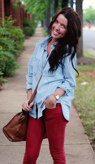 How to wear: light blue denim shirt, red skinny jeans, brown leather duffle bag, tan watch