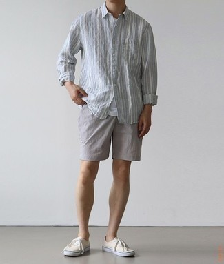 How to Wear Grey Shorts For Men: Go for a light blue vertical striped long sleeve shirt and grey shorts for an off-duty outfit with a contemporary spin. White canvas low top sneakers are a nice choice to finish off your ensemble.