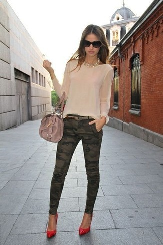A cream long sleeve blouse and dark green skinny jeans are a great outfit formula to have in your arsenal. This outfit is complemented perfectly with red leather pumps.