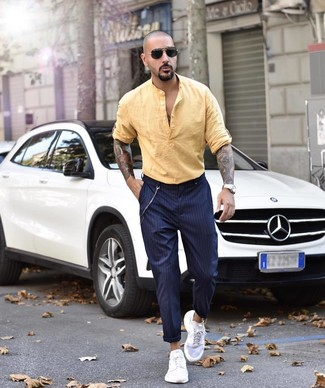 How to wear: yellow linen long sleeve shirt, navy vertical striped chinos, white athletic shoes, black sunglasses