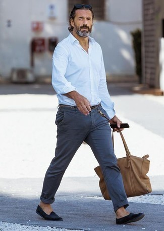 How to Wear a Brown Leather Tote Bag For Men: Combining a light blue long sleeve shirt and a brown leather tote bag will allow you to show your skills in menswear styling even on dress-down days. Go the extra mile and shake up your ensemble by rounding off with a pair of navy velvet loafers.