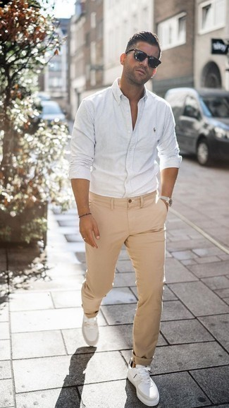 Men's Looks & Outfits: What To Wear In 2020: A white vertical striped long sleeve shirt and khaki chinos are an essential pairing for many style-savvy guys. The whole outfit comes together brilliantly if you complete your look with white leather low top sneakers.