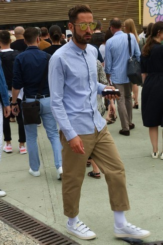 How to Wear Khaki Chinos: Master the casually dapper getup in a light blue long sleeve shirt and khaki chinos. Infuse a bit more edginess into your getup by sporting a pair of white leather low top sneakers.