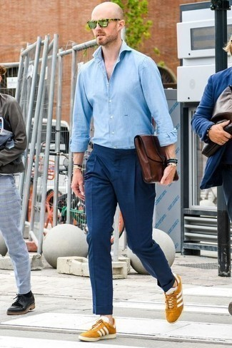 How to Wear a Light Blue Chambray Long Sleeve Shirt For Men: A light blue chambray long sleeve shirt and navy chinos teamed together are a perfect match. Tobacco suede low top sneakers will give a more laid-back vibe to an otherwise dressy ensemble.