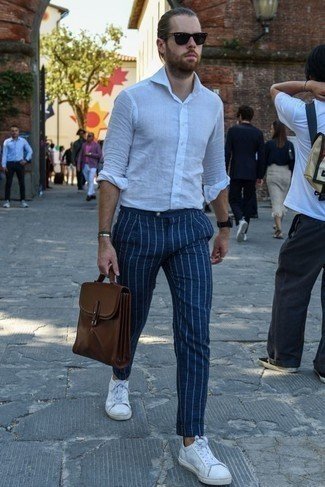 How to Wear White Leather Low Top Sneakers Casually For Men: You'll be amazed at how extremely easy it is for any guy to get dressed this way. Just a white linen long sleeve shirt paired with navy vertical striped chinos. Now all you need is a pair of white leather low top sneakers.