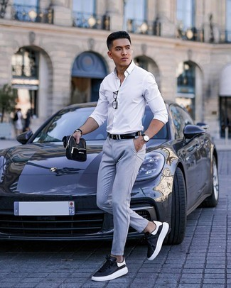 Men's Outfits 2020: If you're scouting for a relaxed but also on-trend outfit, choose a white long sleeve shirt and light blue chinos. For something more on the casually cool side to finish this outfit, add black and white leather low top sneakers to the mix.