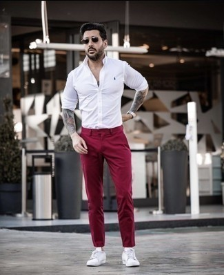 Red Chinos Outfits: Opt for a white long sleeve shirt and red chinos for a daily outfit that's full of charm and personality. Does this getup feel too classic? Let white canvas low top sneakers mix things up a bit.