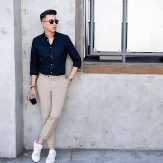 Navy Long Sleeve Shirt Outfits For Men: Fashionable and comfortable, this off-duty combination of a navy long sleeve shirt and beige chinos will provide you with excellent styling possibilities. Finishing off with a pair of white canvas low top sneakers is a surefire way to inject a fun touch into this outfit.