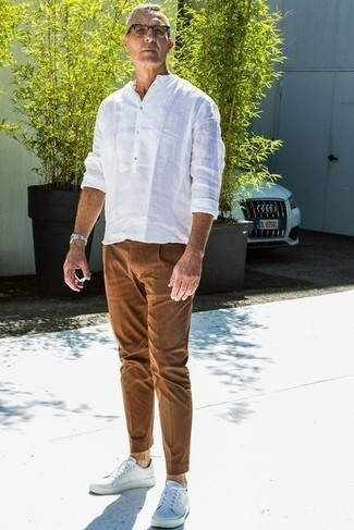1200+ Hot Weather Outfits For Men: This combination of a white linen long sleeve shirt and brown chinos is hard proof that a straightforward casual look doesn't have to be boring. To give your overall outfit a more relaxed touch, why not add a pair of white leather low top sneakers to the mix?