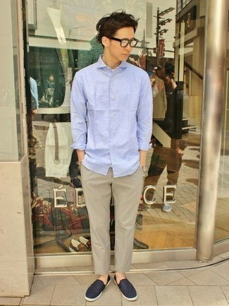 Men's Outfits 2021: This casual combination of a light blue long sleeve shirt and beige chinos is a real life saver when you need to look casually dapper in a flash. A pair of navy canvas slip-on sneakers integrates smoothly within a multitude of getups.