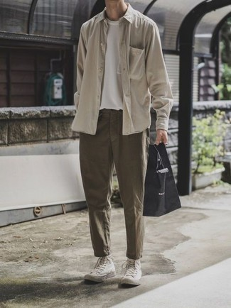 How to Wear a Bag For Men: A beige long sleeve shirt and a bag are the kind of a fail-safe casual look that you so terribly need when you have no time. For footwear, stick to a classier route with a pair of white canvas high top sneakers.