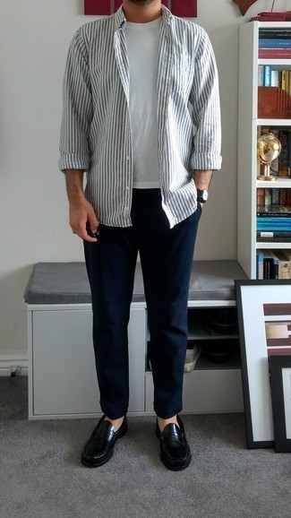 Black Leather Loafers Outfits For Men: A white vertical striped long sleeve shirt and navy chinos are a combination that every modern gentleman should have in his casual sartorial collection. Complete your look with a pair of black leather loafers to avoid looking too casual.