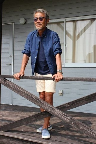 How to Wear Beige Linen Shorts For Men: If you like relaxed combos, why not take this pairing of a blue chambray long sleeve shirt and beige linen shorts for a walk? A pair of light blue slip-on sneakers is a savvy idea to complete your outfit.
