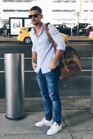 How to Wear a Brown Holdall For Men: You'll be surprised at how easy it is for any gent to put together a laid-back look like this. Just a light blue long sleeve shirt and a brown holdall. Take your look down a whole other path by rounding off with white leather low top sneakers.