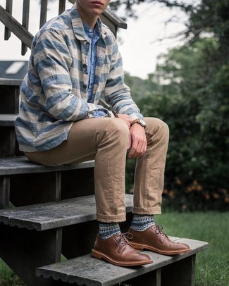 Brown Leather Derby Shoes Outfits: This combo of a light blue chambray long sleeve shirt and khaki chinos spells comfort and casual dapperness. Avoid looking too casual by finishing off with a pair of brown leather derby shoes.