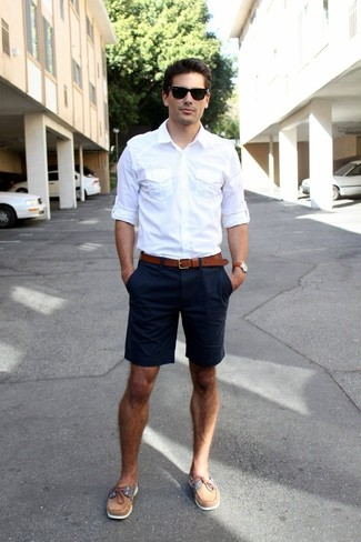 Pairing a white long sleeve shirt with dark blue shorts is a comfortable option for running errands in the city. This outfit is complemented perfectly with brown leather topsiders.