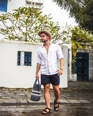 Men's Looks & Outfits: What To Wear In 2020: This off-duty combination of a white linen long sleeve shirt and black shorts is a never-failing option when you need to look great in a flash. Black canvas sandals add a little edge to your ensemble.