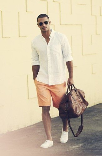 For an outfit that provides comfort and fashion, consider wearing a white long sleeve shirt and orange print shorts. A pair of slip-on sneakers fits right in here. We're loving that this outfit is great come summertime.