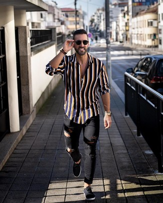 How to wear: navy vertical striped long sleeve shirt, black ripped skinny jeans, black canvas low top sneakers, black sunglasses