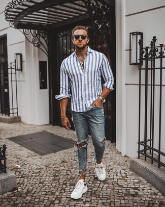 How to Wear a White and Blue Vertical Striped Long Sleeve Shirt For Men: Choose a white and blue vertical striped long sleeve shirt and blue ripped skinny jeans to be both city casual and practical. Turn up the classiness of your outfit a bit by rounding off with a pair of white and black leather low top sneakers.