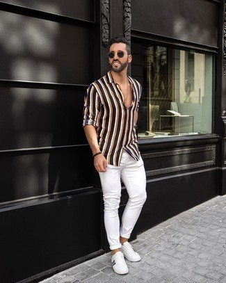 White Skinny Jeans Outfits For Men: One of the coolest ways for a man to style a navy vertical striped long sleeve shirt is to pair it with white skinny jeans for an off-duty combination. For something more on the elegant end to round off your look, complement your ensemble with a pair of white print canvas low top sneakers.