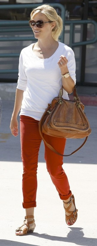 Reese Witherspoon wearing White Long Sleeve T-shirt, Red Chinos, Brown Leather Gladiator Sandals, Brown Leather Satchel Bag