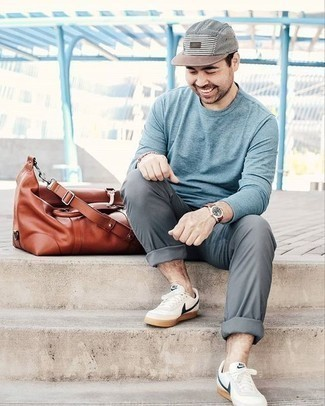 How to Wear a Leather Holdall For Men: Try pairing a light blue long sleeve t-shirt with a leather holdall for a laid-back take on casual street combinations. Take this outfit in a more elegant direction by rounding off with white and navy leather low top sneakers.