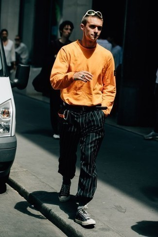 Belt Outfits For Men: If you're scouting for a street style yet sharp getup, dress in an orange long sleeve t-shirt and a belt. Introduce black and white canvas low top sneakers to the mix to avoid looking too casual.