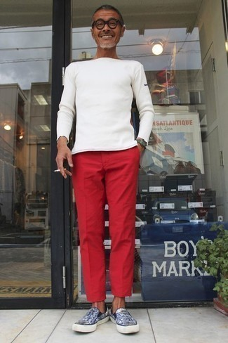 Red Chinos Outfits: A white long sleeve t-shirt and red chinos are essential in any modern man's great off-duty closet. If not sure about what to wear when it comes to shoes, complete your outfit with a pair of navy print canvas slip-on sneakers.