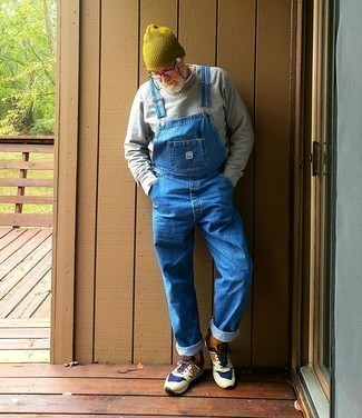 Blue Denim Overalls Outfits For Men: A grey long sleeve t-shirt and blue denim overalls will add extra cool to your daily off-duty routine. For extra style points, introduce a pair of multi colored athletic shoes to the mix.