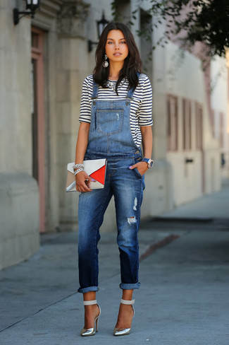 Pairing a white and navy striped long sleeve t-shirt with navy denim overalls is a comfortable option for running errands in the city. A cool pair of metallic pumps is an easy way to upgrade your look.