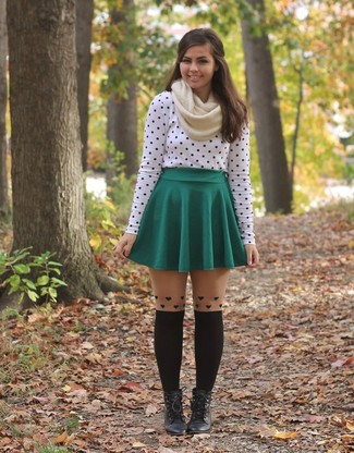 Pairing a white and black polka dot long sleeve t-shirt with a green pleated skirt is a comfortable option for running errands in the city. Make black leather lace-up ankle boots your footwear choice to instantly up the chic factor of any outfit.