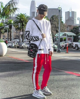 How to wear: white and black print long sleeve t-shirt, red and white vertical striped sweatpants, black and white athletic shoes, black canvas messenger bag